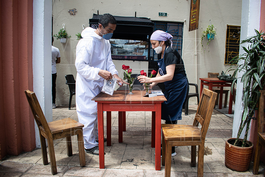 "BOGOTA - COLOMBIA, 05-09-2020: Meseros alistando una mesa durante el primer día del piloto de apertura de restaurantes y cafés al aire libre, denominado ""Bogotá a Cielo Abierto"", en el Chorro de Quevedo en el centro de Bogotá que ahora tiene sus calles pintadas con formas geométricas en pintura neón y cuenta con mesas, distribuidas estratégicamente para mantener el distanciamiento físico al finalizar la cuarentena total en el territorio colombiano causada por la pandemia  del Coronavirus, COVID-19. / Waiters setting up a table during the first day of the pilot for the opening of restaurants and outdoor cafes, called ""Bogotá a Cielo Abierto"", in Chorro de Quevedo in the center of Bogotá, which now has its streets painted with geometric shapes in neon paint and has tables, strategically distributed to maintain physical distancing at the end of the total quarantine in the Colombian territory caused by the Coronavirus pandemic, COVID-19. Photo: VizzorImage / Johan Rugeles / Cont"