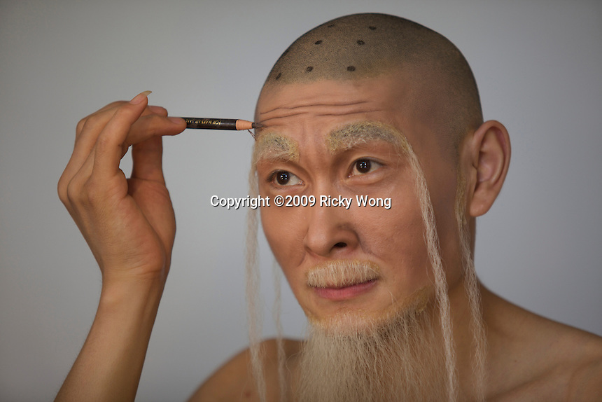 "Martial artist Zheng Xuejin does his make up in the manager's office of Red Theatre. ""Chun Yi: The Legend of Kungfu"" is an entertaining piece of drama, which has been showing for consecutive five years in Beijing, China."