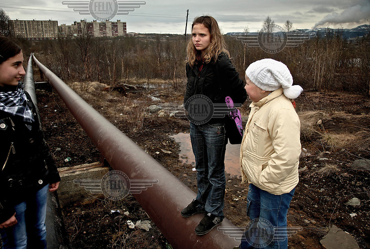 Three young girls stand on hot-water pipes in Zapolyarny, a nickel-processing town in Russia's Arctic. Sulphur dioxide emitted from the factory has killed vegetation, polluted ground water and causes asthma, especially among children. /Felix Features