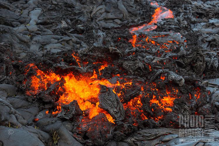 Molten lava breaks through cooled lava in Pulama Pali (of Holei Pali), Hawai'i Volcanoes National Park, Puna district, Hawai'i Island, December 2017.