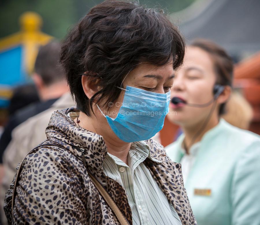 Yangzhou, Jiangsu, China.  Middle-aged Woman Wearing a Breathing Mask.  Slender West Lake Park.