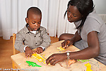 2 year old toddler boy sitting at small table playing with puzzle and toy animals, mother looking on and assisting him