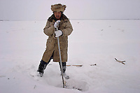 Sikachi-Alyan, Russia, 29/02/2004.&#xD;Drunk man and his two sons subsistance fishing on the frozen Amur River.<br />
