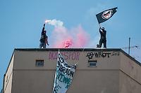 """Bis zu 5.000 Menschen kamen am Samstag den 5 Juli 2014 in Berlin zu einer Demonstration unter dem Motto """"Bleiberecht fuer Alle!"""". Aufgerufen zu der Demonstratiion hatten verschiedene linke und antirassistische Gruppen, nachdem ein Teil Kreuzbergs 10 Tage lang von etwa 1.000 Poliziten abgeriegelt worden war. Der gruene Baustadtrat Kreuzbergs hatte die Raeumung einer von Fluechtlingen besetzten Schule beantragt, wo gegen sich ca. 40 Fluechtlinge und Unterstuetzer zur Wehr gesetzt hatten. Die durch die Absperrungen betroffenen Anwohner der Schule hatten sich mit den Schulbesetzern solidarisiert. Sie wurden von der Polizei 10 Tage lang drangsaliert und konnten nur nach Abgabe ihrer Personalien ihre Wohnungen oder Arbeitsstaetten betreten.<br /> Die Demonstration wurde nach Polizeiangaben von bis zu 890 Beamten aus mehreren Bundeslaendern begleitet, mehrfach kam es zu Festnahmen von Demonstrationsteilnehmern.<br /> Im Bild: Vermummte gruessen die Demonstration mit einer Fahne der Antifaschistischen Aktion und einem sog. """"Bengalo"""".<br /> 5.7.2014, Berlin<br /> Copyright: Christian-Ditsch.de<br /> [Inhaltsveraendernde Manipulation des Fotos nur nach ausdruecklicher Genehmigung des Fotografen. Vereinbarungen ueber Abtretung von Persoenlichkeitsrechten/Model Release der abgebildeten Person/Personen liegen nicht vor. NO MODEL RELEASE! Don't publish without copyright Christian-Ditsch.de, Veroeffentlichung nur mit Fotografennennung, sowie gegen Honorar, MwSt. und Beleg. Konto: I N G - D i B a, IBAN DE58500105175400192269, BIC INGDDEFFXXX, Kontakt: post@christian-ditsch.de<br /> Urhebervermerk wird gemaess Paragraph 13 UHG verlangt.]"""