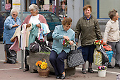 Women try to supplement low incomes and meagre pensions by illegally selling dresses and other items of clothing in the street outside the Kleparz market-place in Krakow.