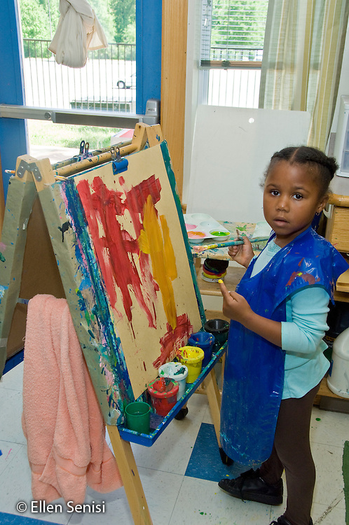 MR / College Park, Maryland.Center for Young Children, laboratory school within the College of Education at the University of Maryland. Full day developmental program of early childhood education for children of faculty, staff, and students at the university..Portrait of girl (5, African American) painting on easel during free time..MR: Smi26.© Ellen B. Senisi