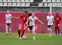 KASHIMA, JAPAN - AUGUST 2: Rose Lavelle #16 of the United States battles for the ball with Janine Beckie #16 of Canada during a game between Canada and USWNT at Kashima Soccer Stadium on August 2, 2021 in Kashima, Japan.