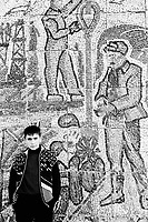 Azerbaijan. Baku Region. Sahil is distant 35 km from Baku. A young man stands close to an old mosaic wall celebrating the blue-collar oil workers, the oil fields and oil-extracting infrastructure, the drilling derricks and rigs.  Mosaic is the art of decoration with small pieces of colored glass, stone or other material. The mosaic were made during the Soviet Union time. © 2007 Didier Ruef
