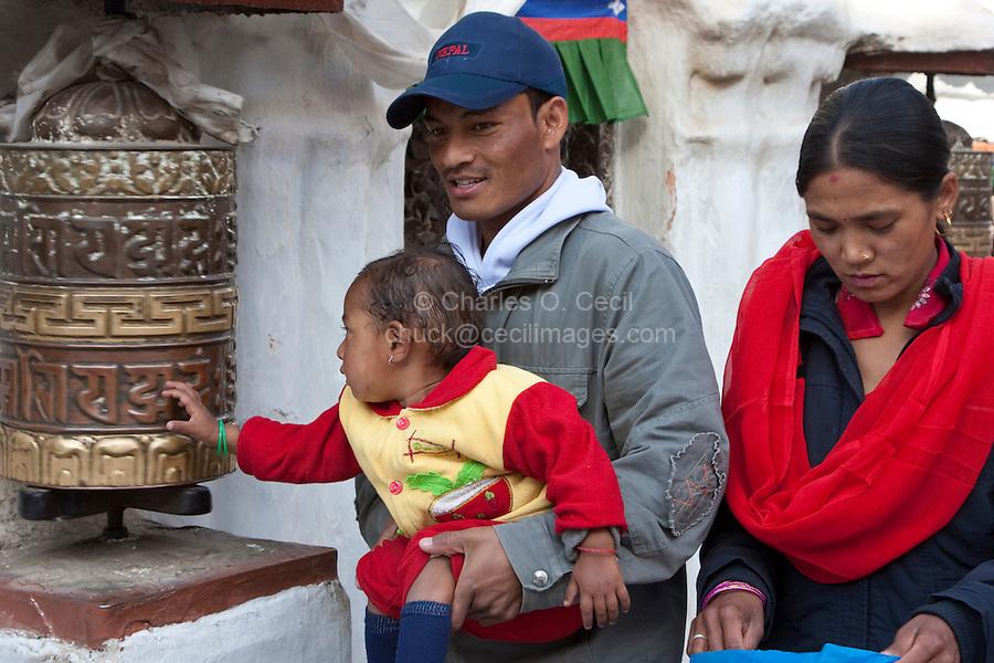 Bodhnath, Nepal.  Buddhist Parents Allowing Child to Turn Prayer Wheel.