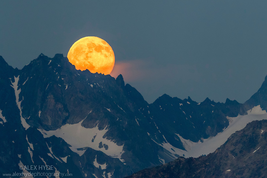 Full moon rising over the Verpeilspitze (3430m). This peak is part of the Glockturmkamm, the westernmost ridge of the Otztal Alps. Nordtirol, Austrian Alps. July. Digitally stitched panorama.