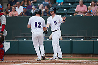 Gunnar Troutwine (12) of the Winston-Salem Dash is greeted at home plate by teammate Alex Destino (23) after scoring a run during the game against the Hickory Crawdads at Truist Stadium on July 7, 2021 in Winston-Salem, North Carolina. (Brian Westerholt/Four Seam Images)