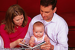 8 month old baby girl with parents interested in board book they are reading to her horizontal
