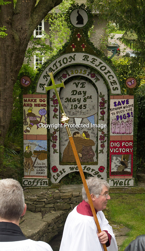 14/05/15<br /> <br /> Clergy bless the V.E. Day inspired design, at Coffin Well - named after the shape of the well.<br /> <br /> To mark ascension day this year's well dressings are unveiled and blessed by the local clergy in the Derbyshire village of Tissington in the Peak District National Park.<br /> <br /> Before today's blessings, wooden boards coated in clay are decorated with tens of thousands of petals, leaves and pieces of foliage to create the giant intricate mosaics. The boards,  take teams of many villagers three days to make. <br /> <br /> The village has been decorating its six wells every year for more than six hundred years. The tradition is believed to be a celebration of the wells never running dry, giving life and  sustaining the village during times of plague. After a church service today (Thursday)  clergy from six parish will bless each of the well.  <br /> <br /> Following in Tissington's footsteps many other villages in the Derbyshire area also have their own well dressing traditions.<br /> <br /> <br /> All Rights Reserved: F Stop Press Ltd. +44(0)1335 418629   www.fstoppress.com.