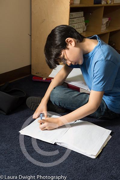 Boy writing sitting on floor Education Elementary Grade 5