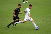 LOS ANGELES, CA - OCTOBER 25: Cristian Pavon #10 of the Los Angeles Galaxy passes off the ball during a game between Los Angeles Galaxy and Los Angeles FC at Banc of California Stadium on October 25, 2020 in Los Angeles, California.