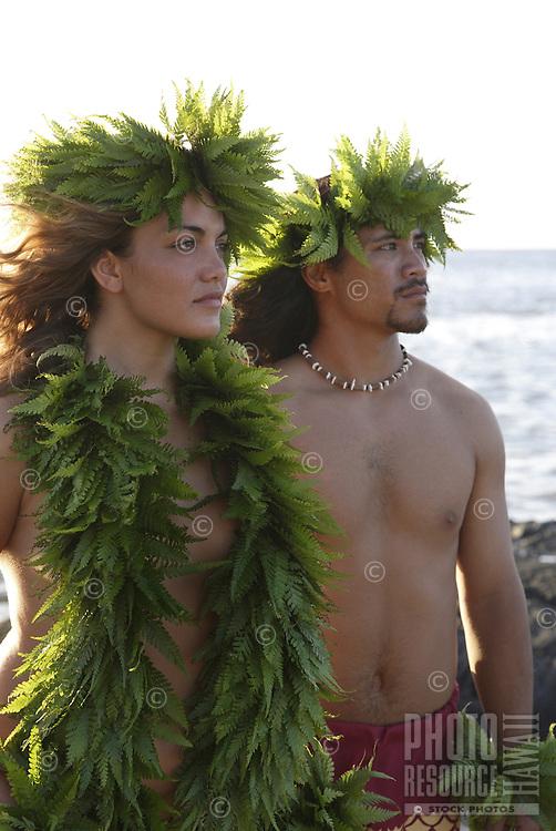 Wahine (female) and kane (male) hula dancers deep in thought, wearing palapalai fern head lei, headshot.