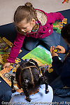 Preschool 3-4 year olds two girls and a boy working together playing with floor puzzle vertical
