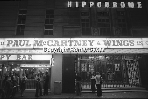 """Paul and Linda McCartney Wings Tour 1975. Fans wait outside the the Hippodrome theatre. Paul McCartney and Wings in Concert, Bristol, England The photographs from this set were taken in 1975. I was on tour with them for a children's """"Fact Book"""". This book was called, The Facts about a Pop Group Featuring Wings. Introduced by Paul McCartney, published by G.Whizzard. They had recently recorded albums, Wildlife, Red Rose Speedway, Band on the Run and Venus and Mars. I believe it was the English leg of Wings Over the World tour. But as I recall they were promoting,  Band on the Run and Venus and Mars in particular."""