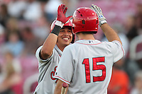 Spokane Indians infielder Edwin Garcia #1 is greeted by first baseman Brett Nicholas #15 after hitting a home run against the Salem-Keizer Volcanoes at Volcanoes Stadium on August 10, 2011 in Salem-Keizer,Oregon. Salem-Keizer defeated Spokane 7-6.(Larry Goren/Four Seam Images)