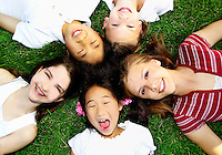 Five diverse children laying on grass with their heads together.