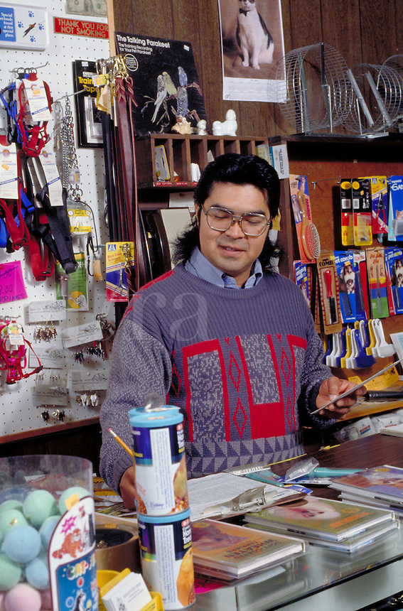 Native American businessman works behind the counter in a bookstore, Berkeley, CA
