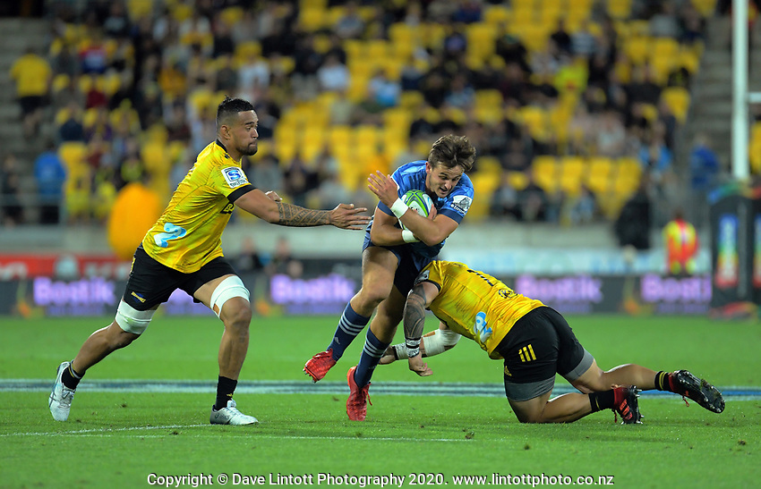 Harry Plummer (Blues) is tackled during the Super Rugby match between the Hurricanes and Blues at Sky Stadium in Wellington, New Zealand on Saturday, 7 March 2020. Photo: Dave Lintott / lintottphoto.co.nz