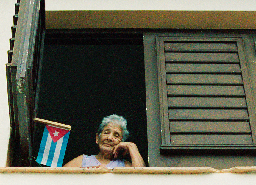 A woman watches the International Workers' May Day parade on the street below in Varadero, Cuba. May 1, 2003. MARK TAYLOR GALLERY.