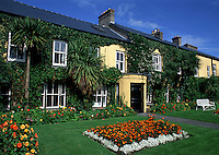 The exterior of an ivy covered Irish house and landscaped garden. Adare, Ireland.