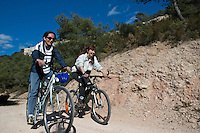 Two women having fun together as they ride their bikes along a dirt road, Vitrolles, Provence, France.