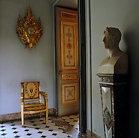 A gilded military-themed clock hangs above a gilt Empire chair in the hallway