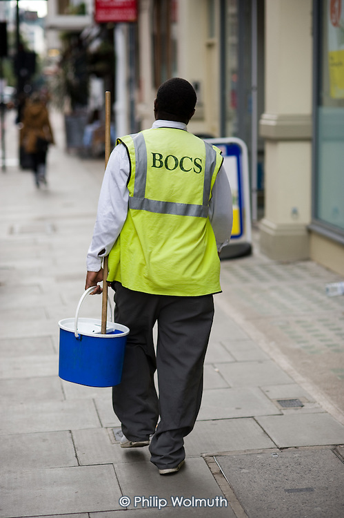 A cleaner with a mop and bucket walks down a street in central London.