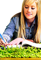 Blonde female teen laying on a green shag rug studying