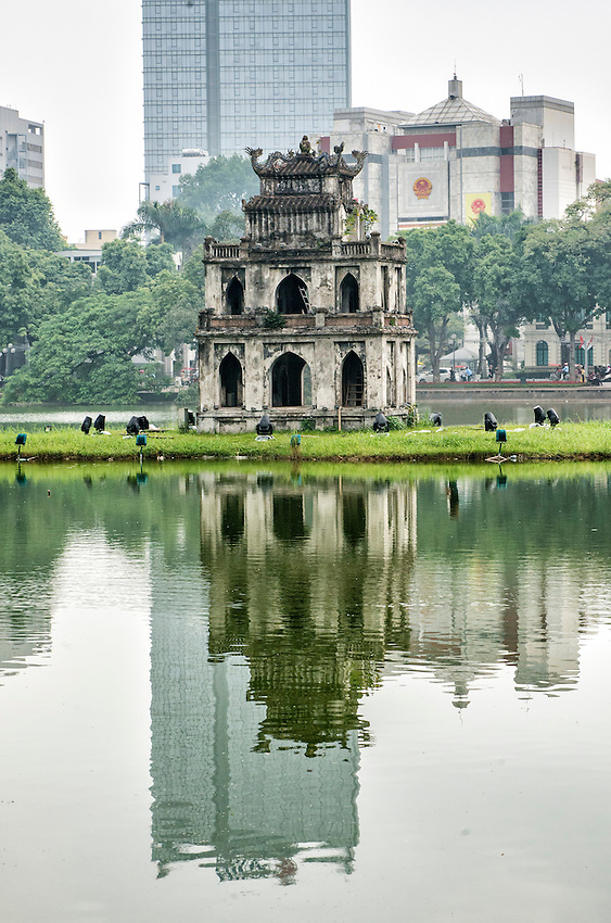 The Turtle Tower stands on a small island in Hoan Kiem Lake, located in the old quarter of Hanoi. Built in 1886, the tower contrasts with the modern buildings behind it which are also reflected here in the lake.