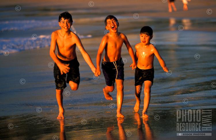 Three boys running on the beach on the Big Island