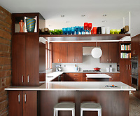 This walnut kitchen ties in nicely with the exposed brick walls and terrazzo floor. A high shelf above the breakfast bar houses a colourful collection of glassware.