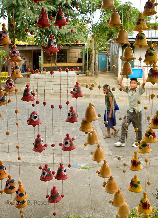 Two Nicaraguan children walk by a cooperative selling ceramics, San Juan de Oriente, Nicaragua