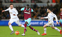 Cheikhou Kouyate of West Ham United goes past Gylfi Sigurdsson and Leon Britton of Swansea City during the Barclays Premier League match between Swansea City and West Ham United played at The Liberty Stadium, Swansea on 20th December 2015