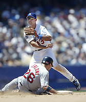 Alex Cora of the Los Angeles Dodgers makes a throw while avoiding Lou Merloni of the Boston Red Sox during a 2002 MLB season game at Dodger Stadium, in Los Angeles, California. (Larry Goren/Four Seam Images)