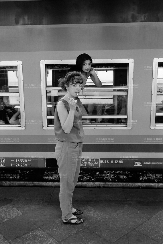 Italy. Lazio Region. Rome. Roma Termini (in Italian, Stazione Termini) is the main railway station of Rome. Both young women are train's passengers. One stands inside the wagon while the other is on the platform smoking a cigarette. Rome is the capital city and a special comune of Italy (named Comune di Roma Capitale), as well as the capital of the Lazio region. 1.06.92  © 1992 Didier Ruef