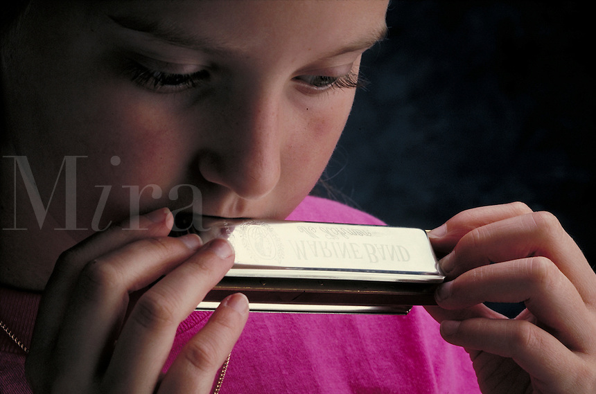 Harmonica played by a young girl.  May not be used in an elementary school dictionary. Cleveland Ohio USA.