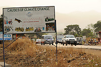 SIERRA LEONE, Freetown, sign board climate change and road with traffic