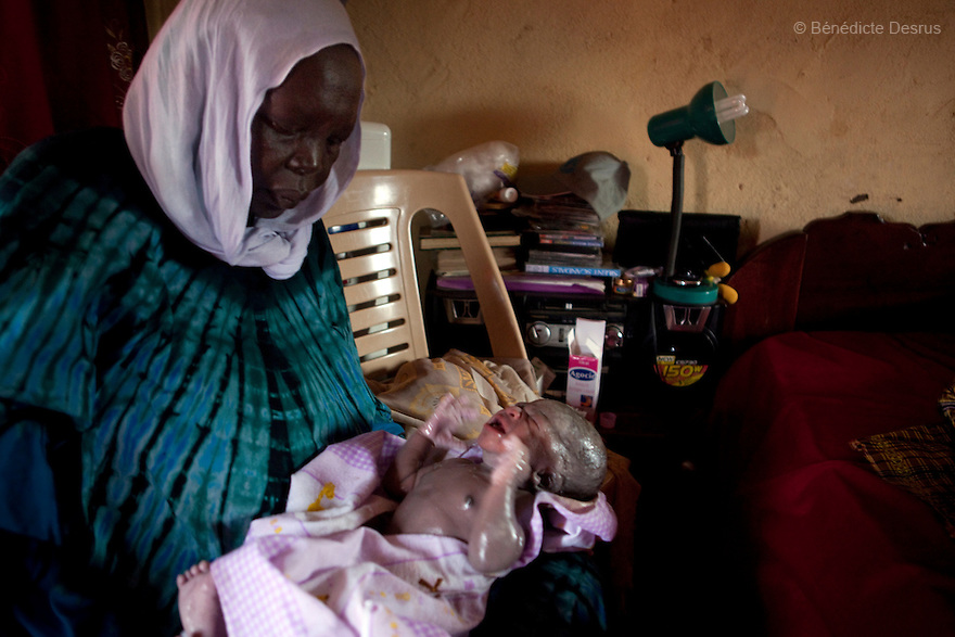 2011 - Juba, Republic of South Sudan - Regabia Ahmad, a qualified birth attendant, takes care of Lushi Rashid's newborn baby at their family home in Juba, the capital city of South Sudan. Regabia has been delivering babies in South Sudan for over twenty years. she was trained by the health ministry and works at a local primary health clinic. With fewer than 100 trained midwives for a population of over eight million, South Sudan has the highest maternal mortality rate in the world.  One in seven South Sudanese women is likely to die because of complications from delivery. Just 10 per cent of South Sudanese women have access to medical professionals during childbirth. Photo credit: Benedicte Desrus