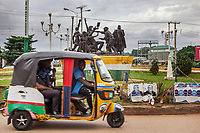 """Nigeria. Enugu State. Enugu. Town center. A tricycle carrying two Igbo policemen with their weapons ride on the road. Both police officers have Kalashnikov rifles which are automatic rifles, widely known as Kalashnikovs, AK47s, or as a """"Kalash». The yellow auto rickshaw is used by """"Keke"""" drivers for transporting people around town. The  tricycle better known in Nigeria as the Keke NAPEP is gaining the dominance on Nigerian roads sweeping every street of cities and villages. The auto rickshaw is a common form of urban transport, both as a vehicle for hire and for private use. The tricycle passes on a roundabout near a monument dedicated to the memory of Enugu coal miners. On the 18th November 1949, 21 striking miners and a bystander were shot dead at a British government-owned coal mine at Enugu, Nigeria; 51 were injured. The miners were fighting for back-pay owed to them for a period of casualisation known as 'rostering', later declared illegal, and had been sacked following a work to rule. They occupied the mine to prevent a repeat of the lock-out they had suffered during the 1945 general strike. Nigerian Coal had been of strategic importance during the war, and continued to be vital in the re-building of infrastructure by the post-war Labour government, who sought to maximise output in the Sterling zone to pay off its debt to the U.S.A. Enugu is the capital of Enugu State, located in southeastern Nigeria. 30.06.19 © 2019 Didier Ruef"""