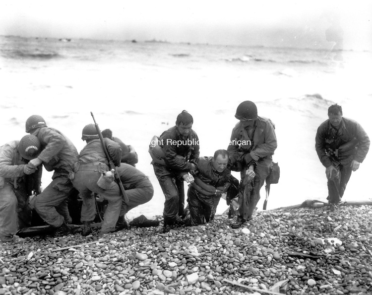 Members of an American landing unit help their exhausted comrades ashore during the Normandy invasion, June 6, 1944. The men reached the zone code-named Utah Beach, near Sainte Mere Eglise, on a life raft after their landing craft was hit and sunk by German coastal defenses.  (AP Photo/International News Photo Pool)