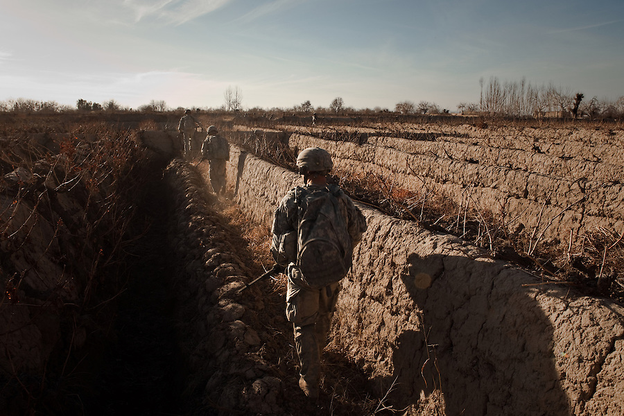 Soldiers with a heavy weapons team - part of Charlie Co. 1st Battalion 12th Infantry Regiment, 4th Infantry Division in Zhari District, Kandahar, Afghanistan - negotiate the district's endless mud walls which partition the vineyards which dominate the area. The violently contested district sits astride the strategically Highway 1 ringroad between Kandahar and Lashkar Gah and is seen by some as the birthplace of the Taliban movement.