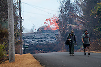 May 2018: Two men wearing gas masks walk away from the Kilauea Volcano eruption in Leilani Estates, Puna, Big Island of Hawai'i.