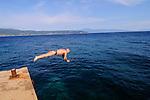 Mann springt, köpfelt ins Wasser. Man jumping into the water. Küste beim Campingplatz von Glavotok; coast at the camping, campsite of Glavotok, Krk Island, Dalmatia, Croatia. Insel Krk, Dalmatien, Kroatien. Krk is a Croatian island in the northern Adriatic Sea, located near Rijeka in the Bay of Kvarner and part of the Primorje-Gorski Kotar county. Krk ist mit 405,22 qkm nach Cres die zweitgroesste Insel in der Adria. Sie gehoert zu Kroatien und liegt in der Kvarner-Bucht suedoestlich von Rijeka.