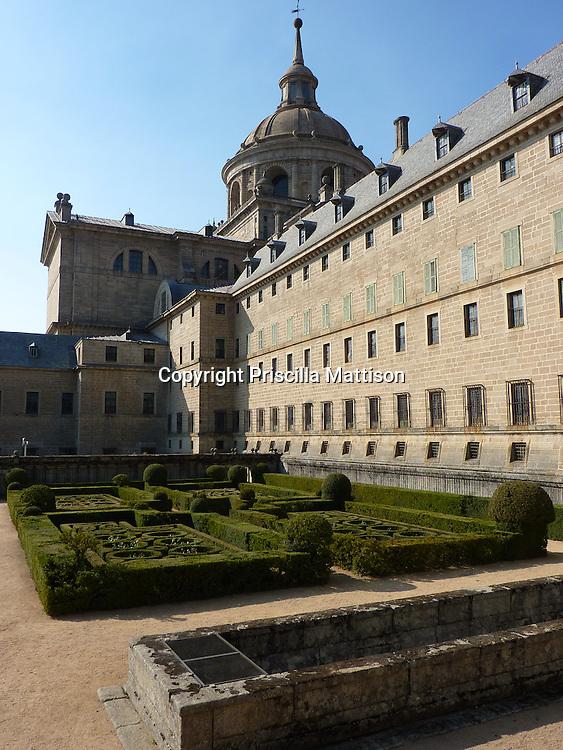 San Lorenzo de El Escorial, Spain - October 18, 2011:  A formal garden enhances the imposing exterior of El Escorial.