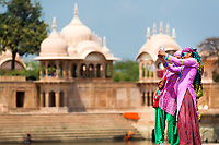 Colorful young women taking a selfie in the famous Kusum Sarovar, on the holy Govardhan Hill between Govardhan and Mathura, Uttar Pradesh, India