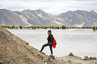 A Tibetan boy stands near the edge of a swollen river near Lhasa. Temperatures are rising on the Tibetan Plateau faster than anywhere else in the world, outside the polar regions. Shrinking glaciers, drying grasslands and a changing way of life are evident in the region, as people here adapt on the front lines of climate change.